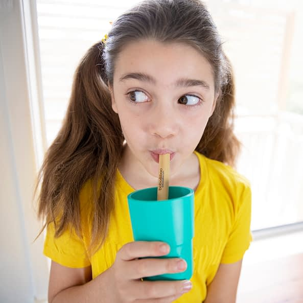 Girl drinking from plant-based cup with bamboo straw
